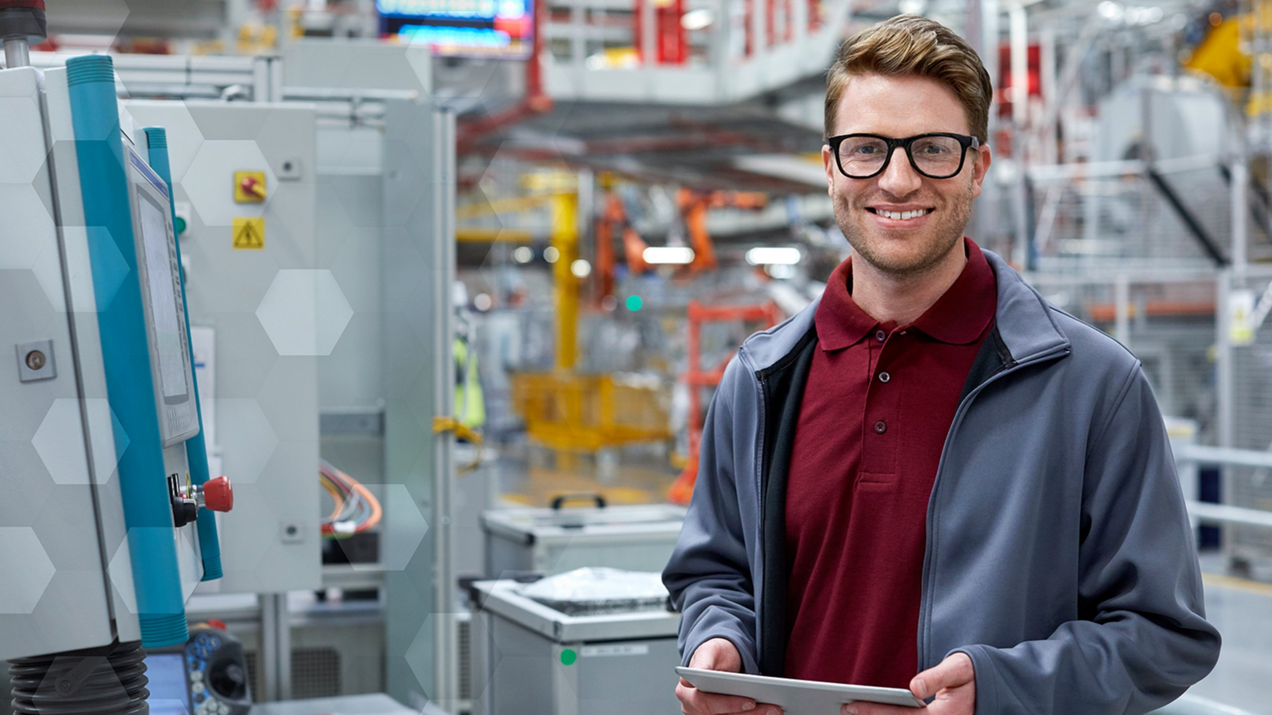 man wearing glasses, red polo, blue jacket holding tablet in factory setting deploying ScanESC lockout/tagout software program