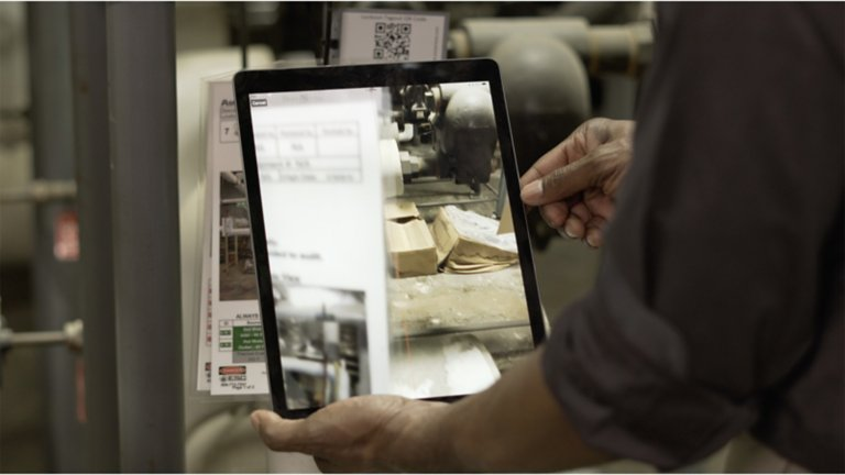 Man in dark shirt using a tablet to scan a lockout/tagout procedure using ScanESC software in a furnace room