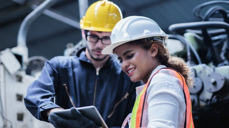 man and woman in safety gear looking at a tablet
