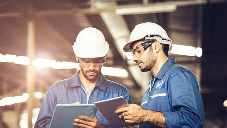 Two men working on an annual lockout/tagout audit in a manufacturing facility