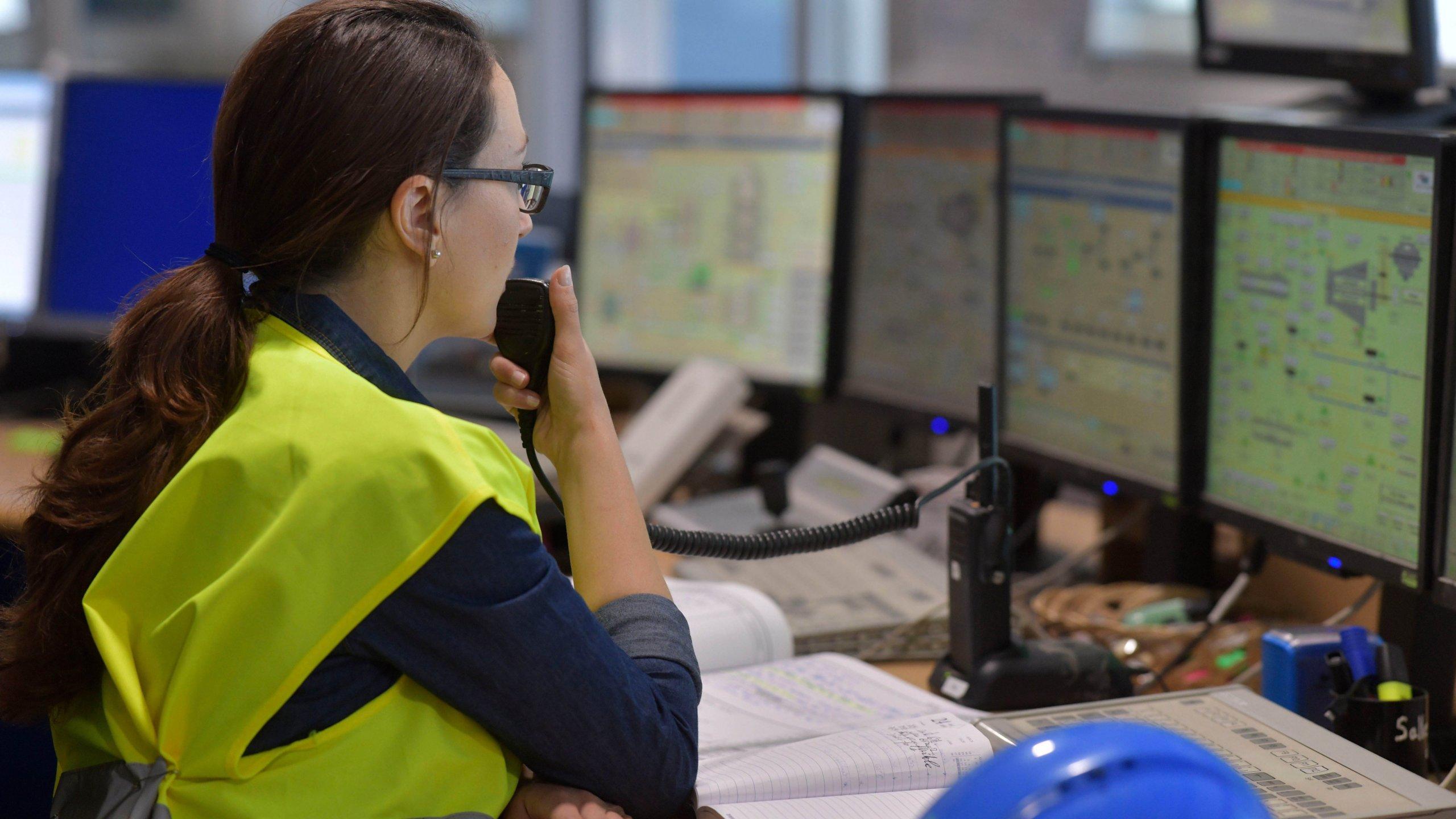 複数のモニタでソフトウェアを監視する女性従業員