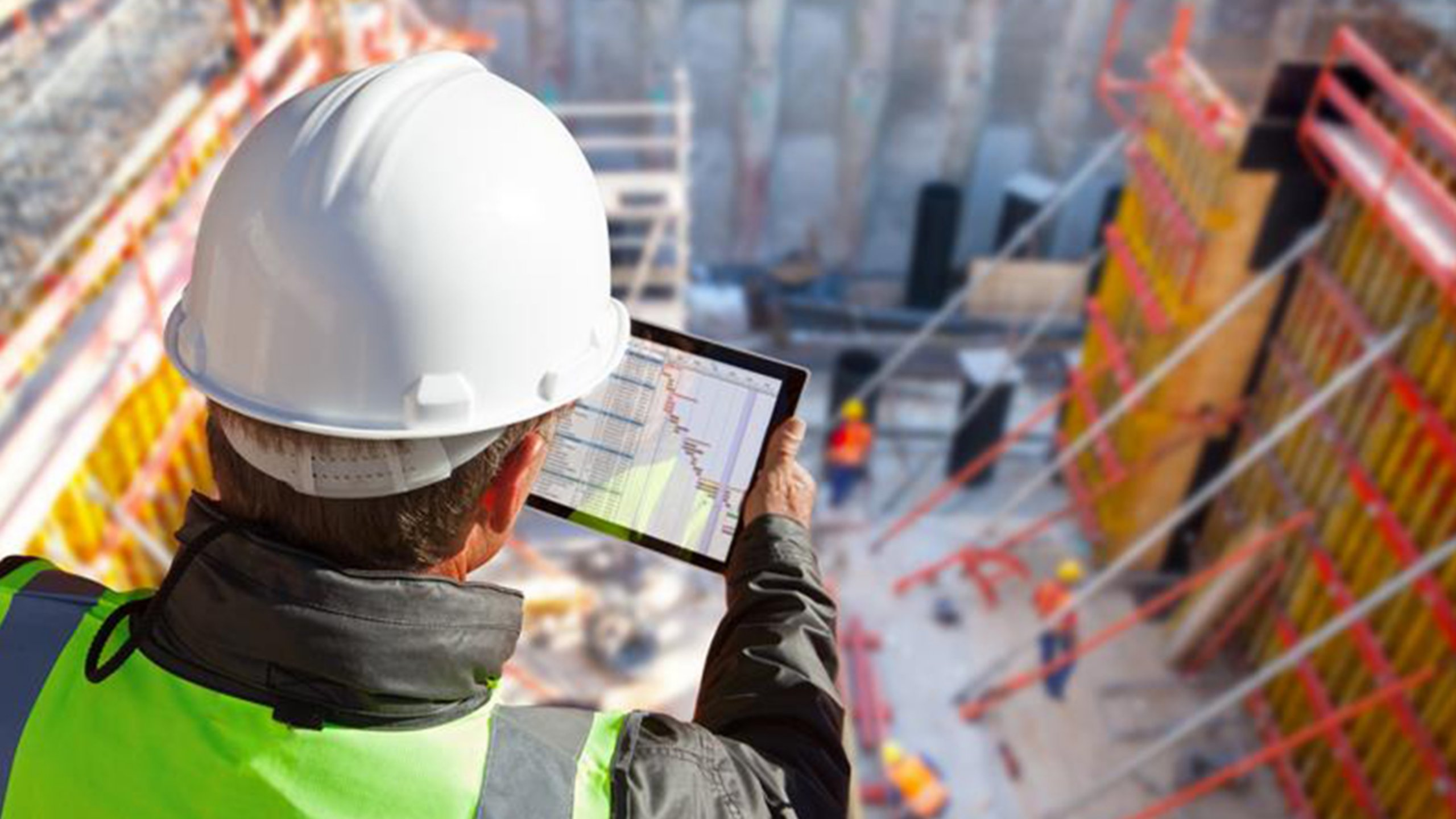 Man wearing a white hard hat holding a touch screen next to a construction site