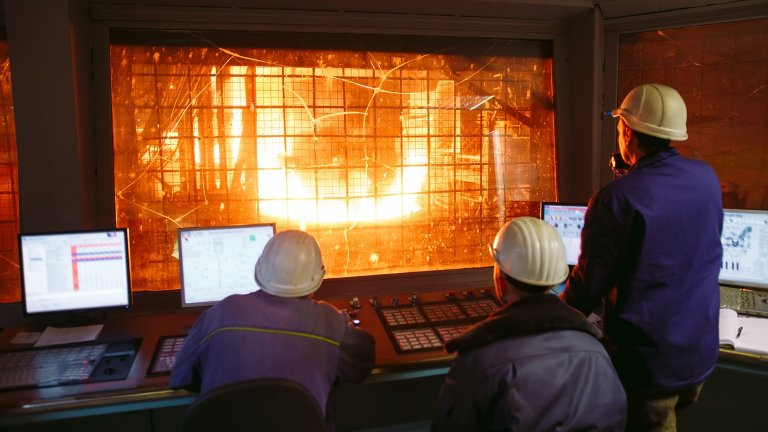Metal workers sitting at a desk overseeing a steel refining process at a steel mill through a window separating them from production