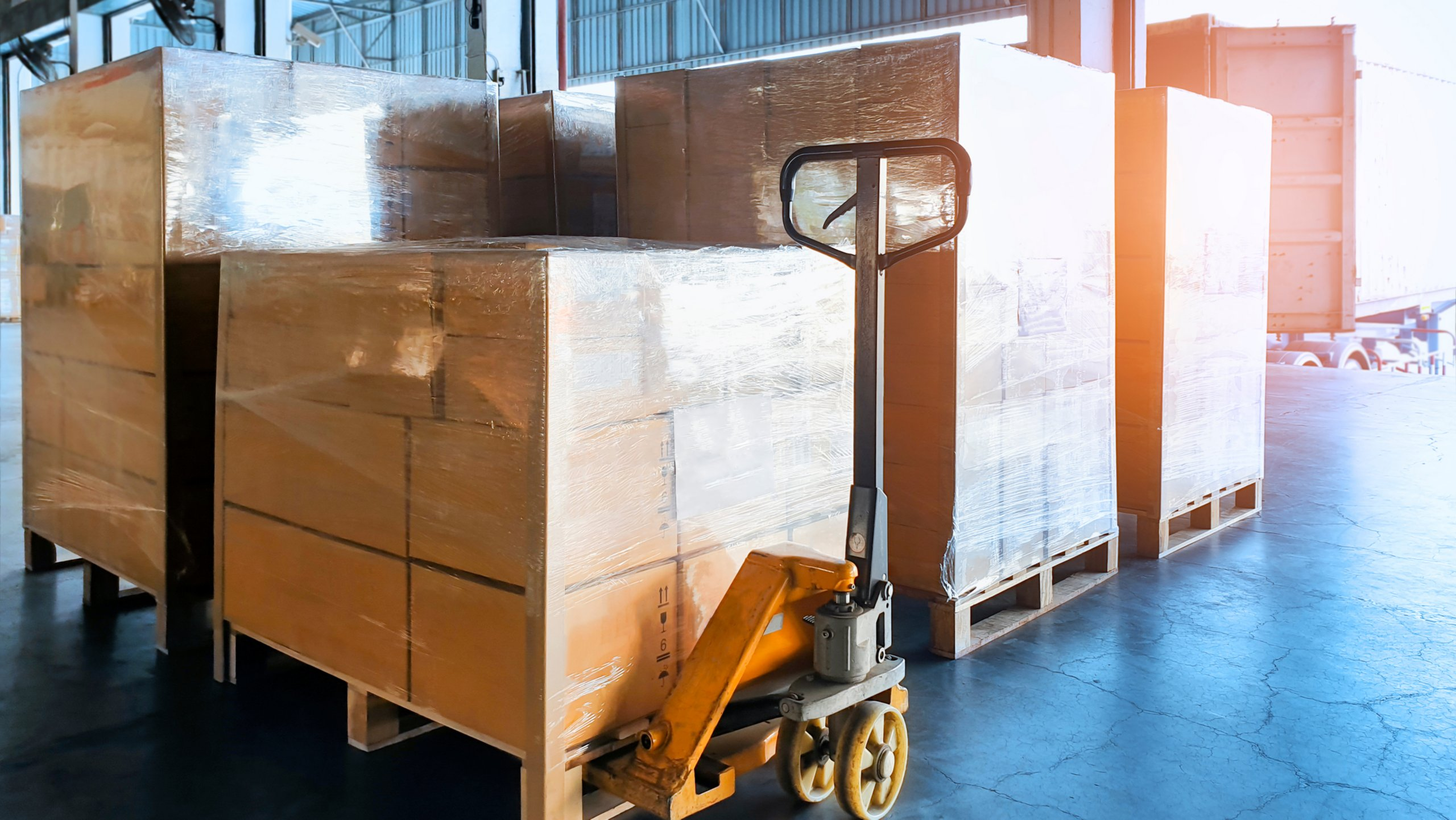 Cardboard boxes stacked and wrapped in plastic for shipping in warehouse