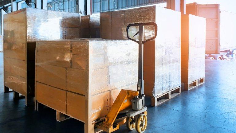 Boîtes en carton emballées dans du plastique et empilées sur un diable dans un entrepôt