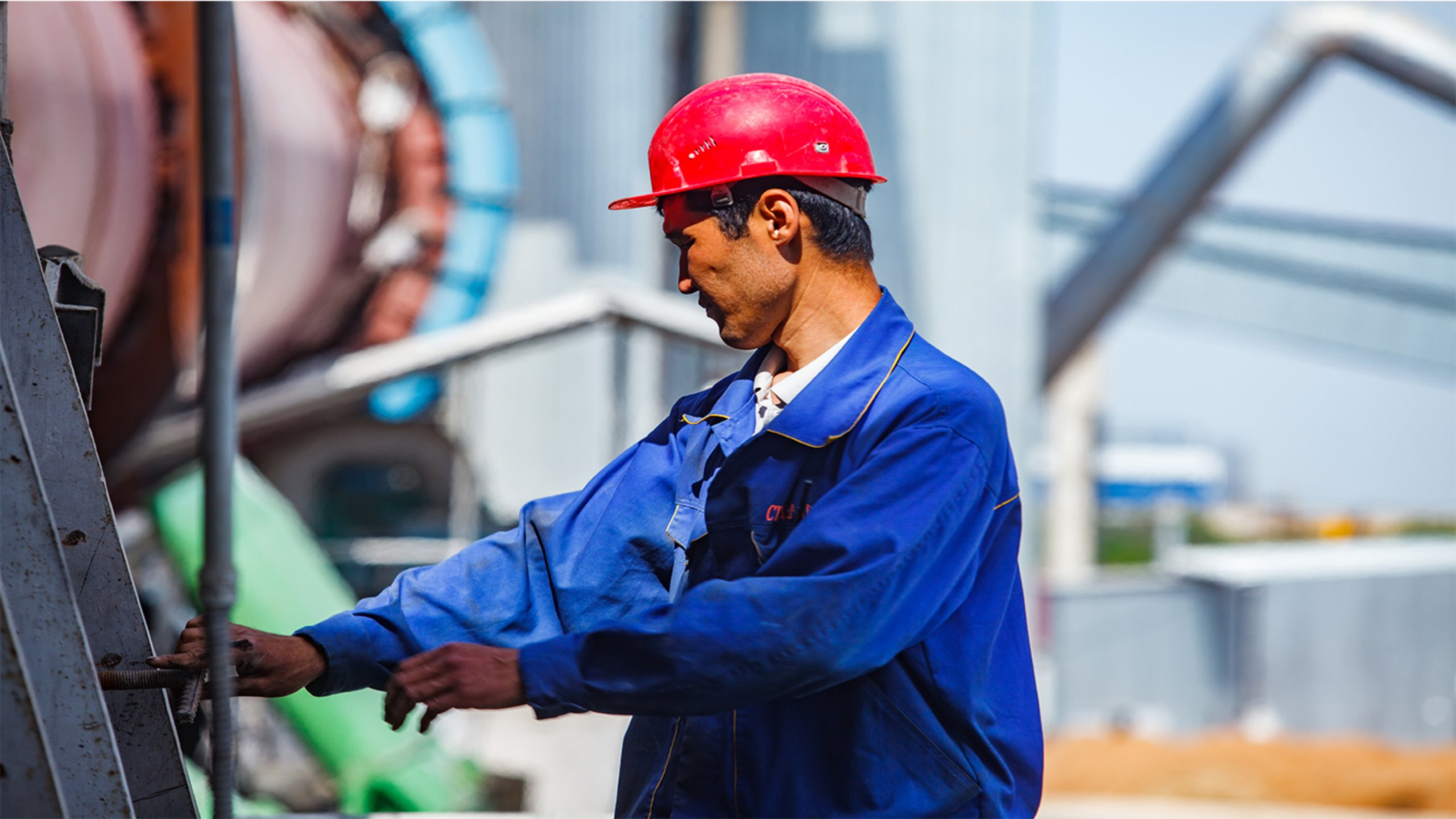 man in blue coverall and red hard hat operating cement kiln