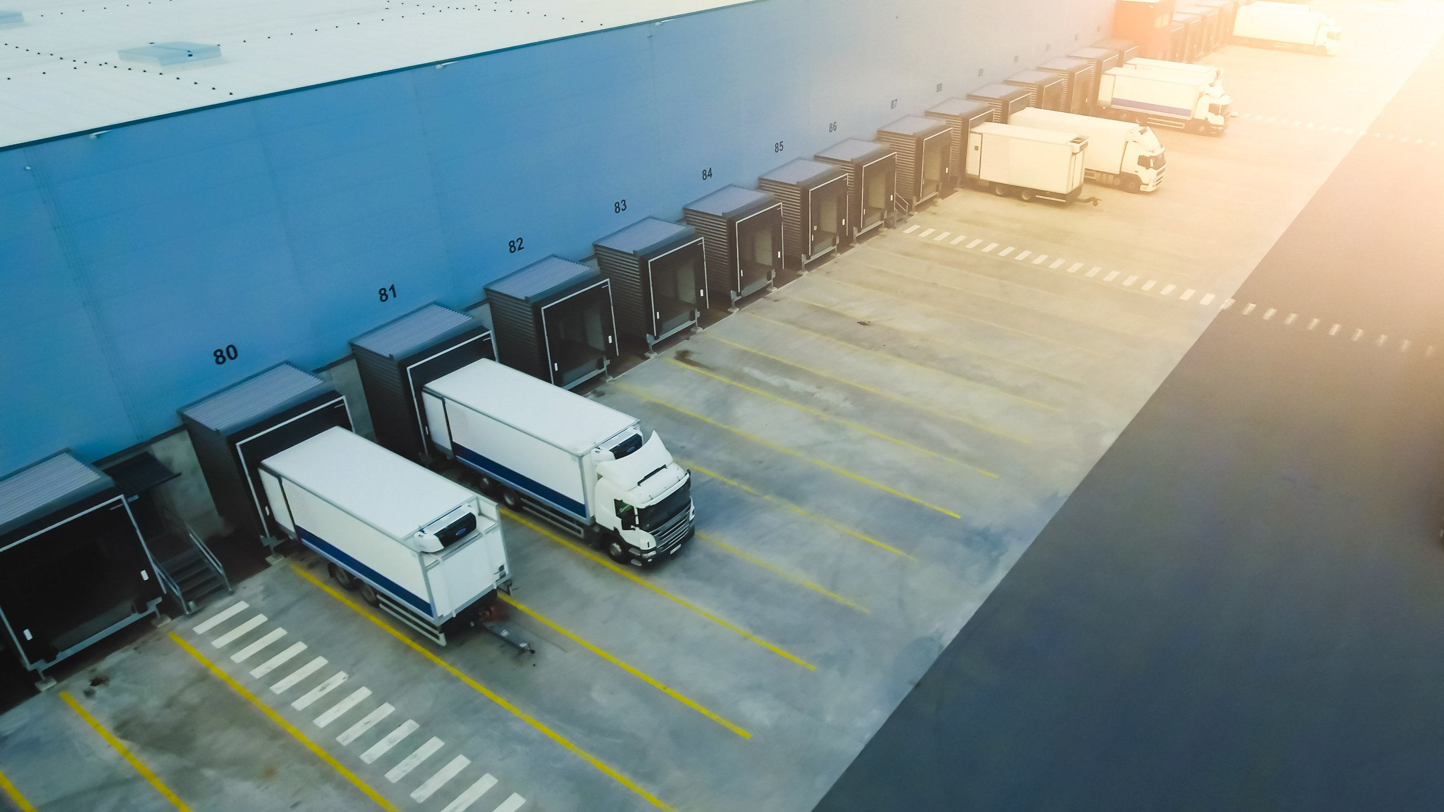 Aerial Shot of Industrial Warehouse Loading Dock where Many Truck with Semi Trailers Load Merchandise.