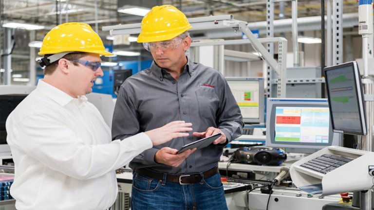 Two men in yellow hard hats and safety glasses in discussion holding tablet in an industrial environment