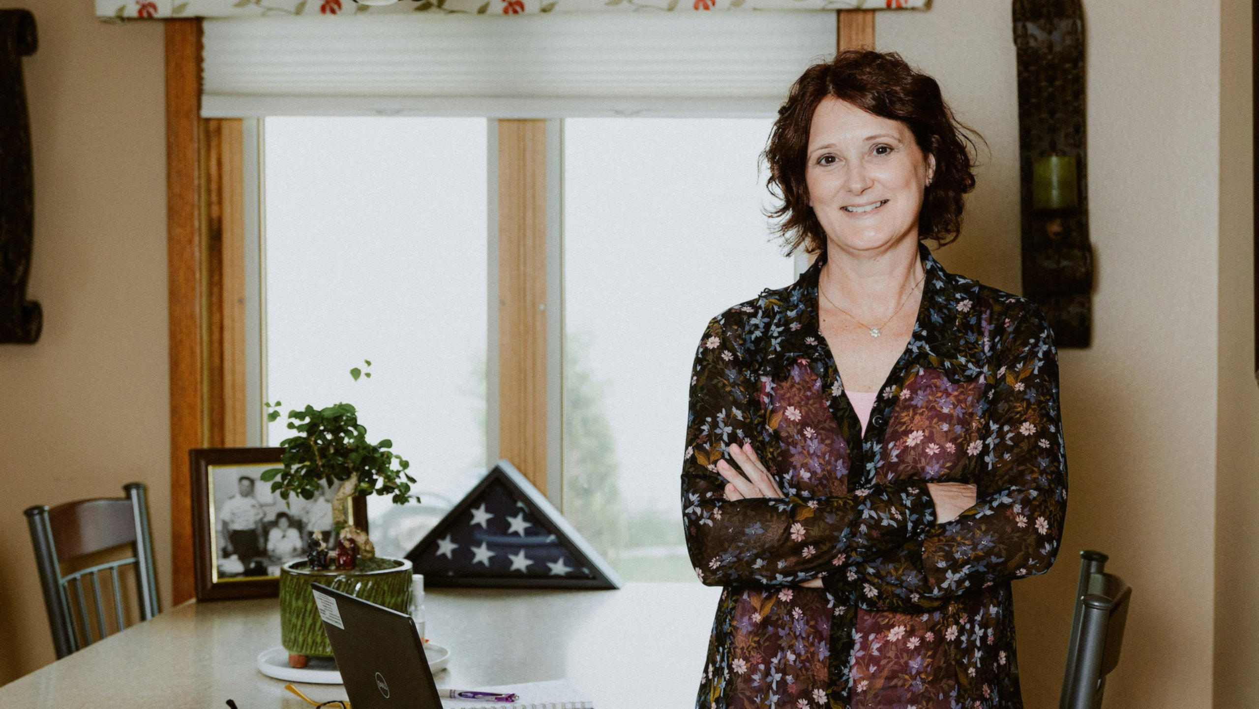 female military veteran employee stands confidently next to her computer while working from home