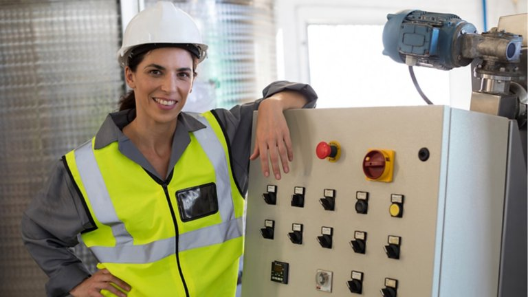 woman in safety vest and hat standing next to push button panel
