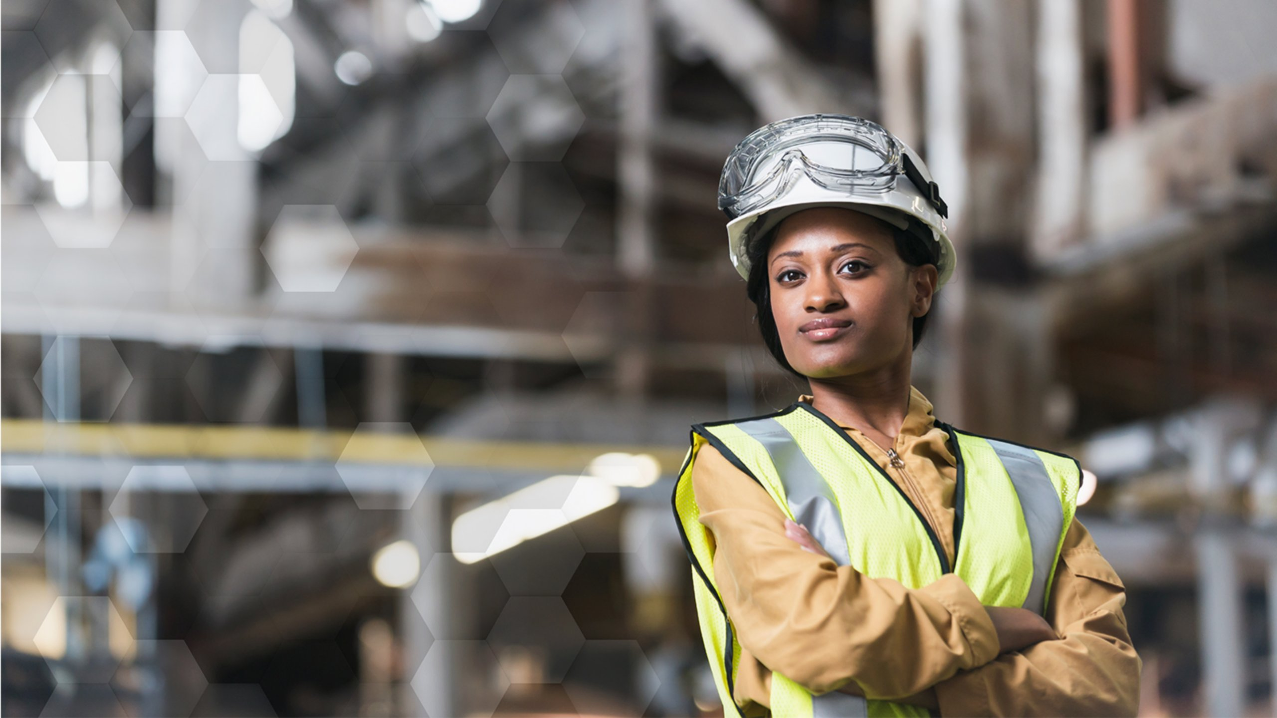 Women wearing hardhat with safety glasses and safety vest in manufacturing facility with lockout/tagout procedures