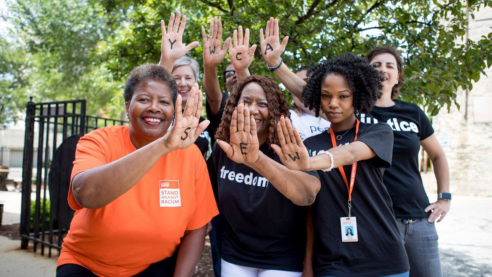 7 YWCA women holding a hand with the letters YWCA SEW on each hand