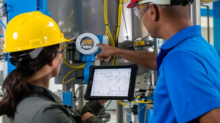 A female and male wearing hard hats in a factory floor viewing a screen with information linked to a machine