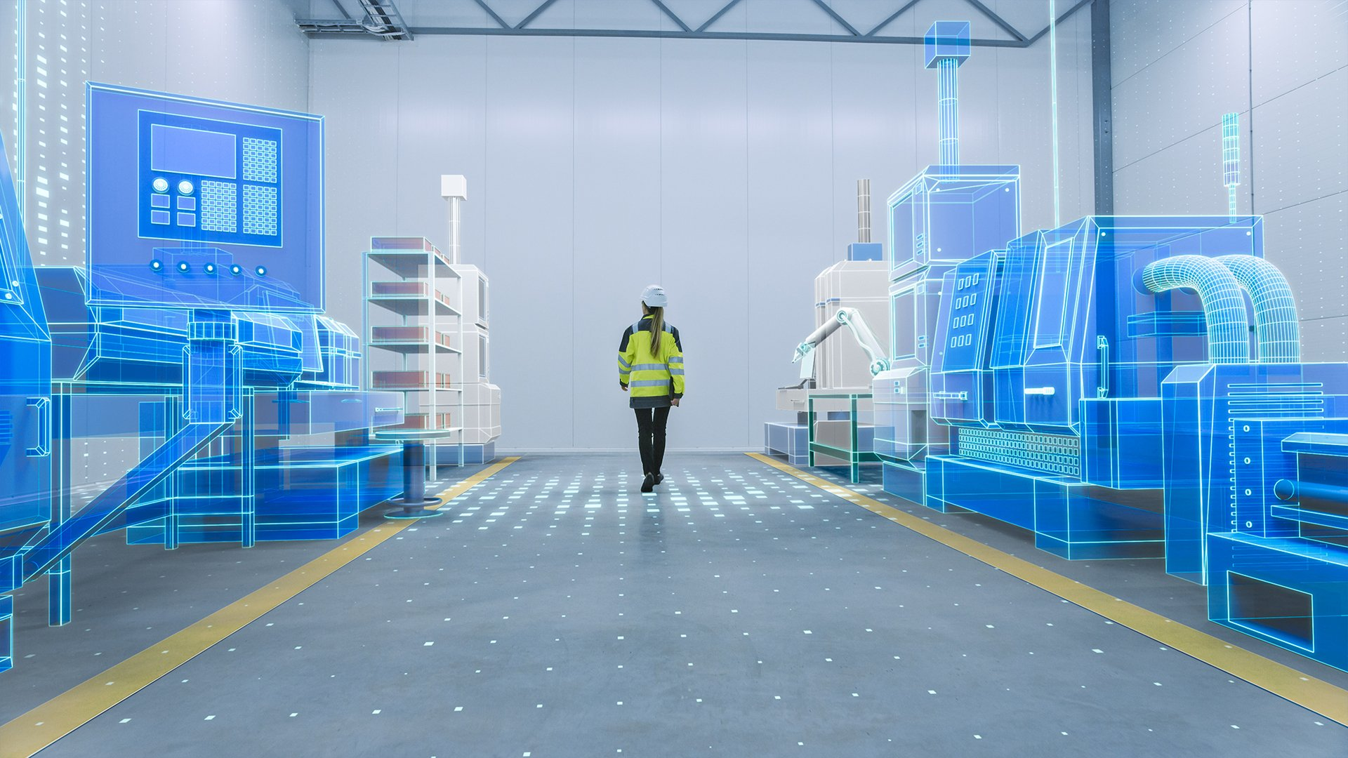 Female employee wearing white hard hat and a yellow safety jacket walking in an aisle of a digitizal plant