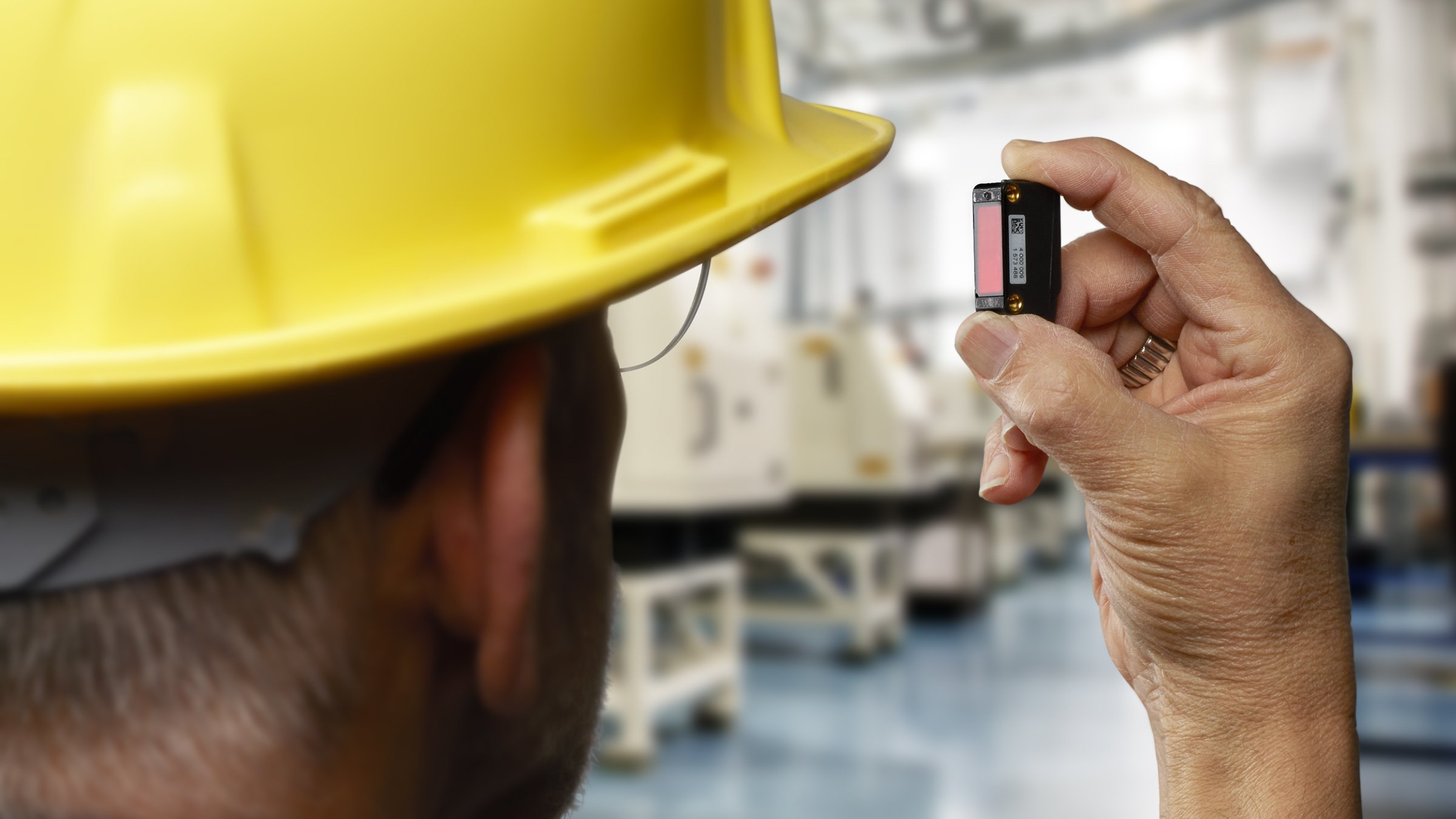An over the shoulder view of a man in a yellow hard hat holding up a black 42JA VisiSight photoelectric sensor.