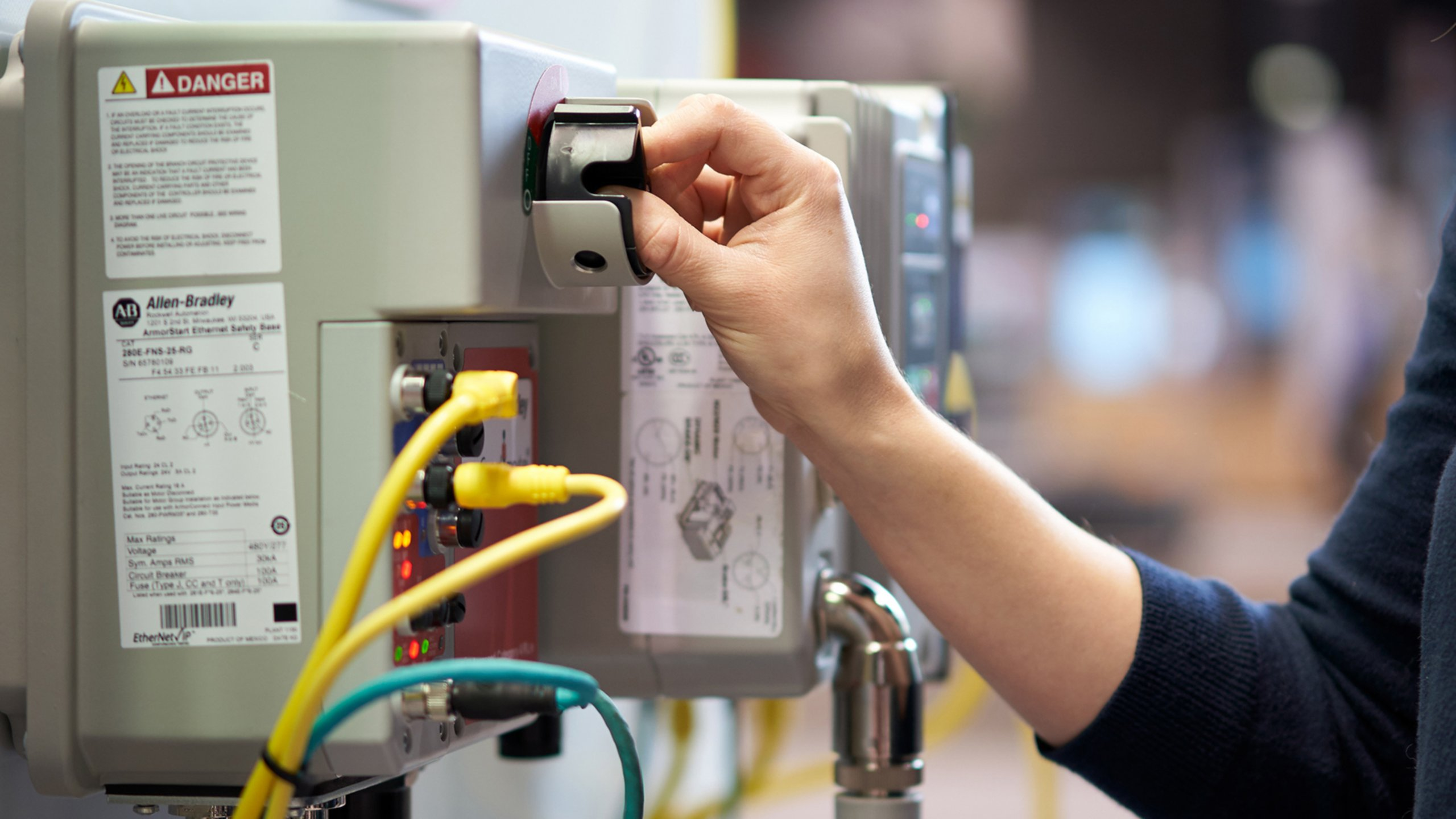 Female hand using a switch in a manufacturing environment