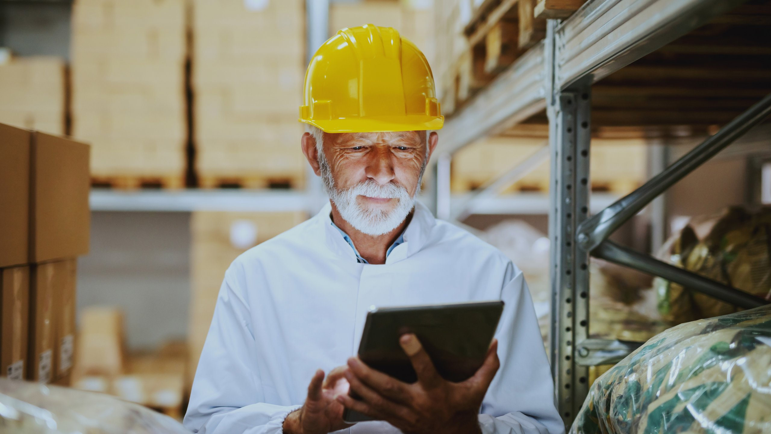 Caucasian senior adult employee in white uniform and with yellow helmet on head checking on goods in warehouse by using tablet.
