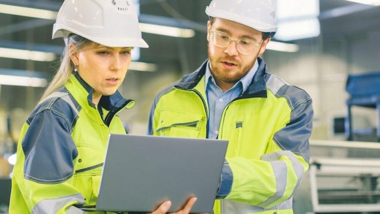 노트북의 소프트웨어를 바라보는 두 명의 공장 직원
