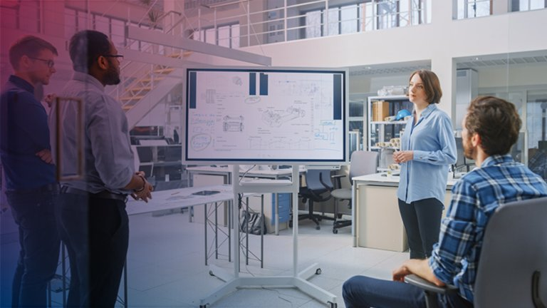 Group of employees in a meeting viewing charts with data on a large monitor.