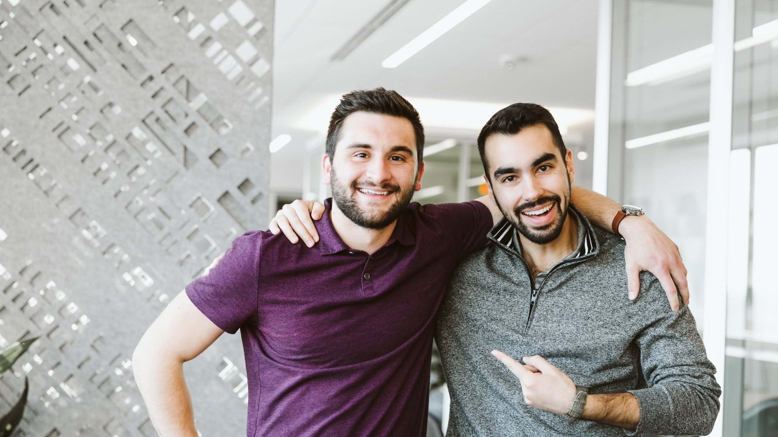 Two young men coworkers embrace casually in an office setting at Rockwell Automation