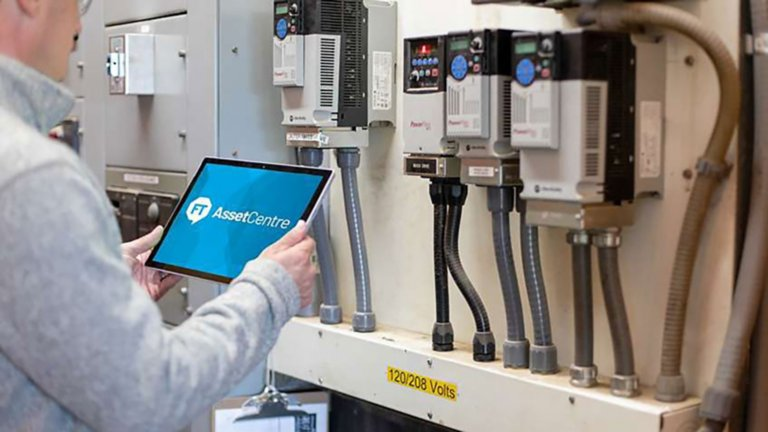 Engineer looking at FactoryTalk AssetCentre software on his tablet in front of Rockwell Automation products in the factory