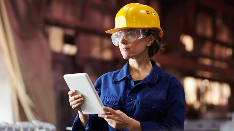 Woman wearing hard hat and safety glasses and looking at a tablet, in a manufacturing environment.