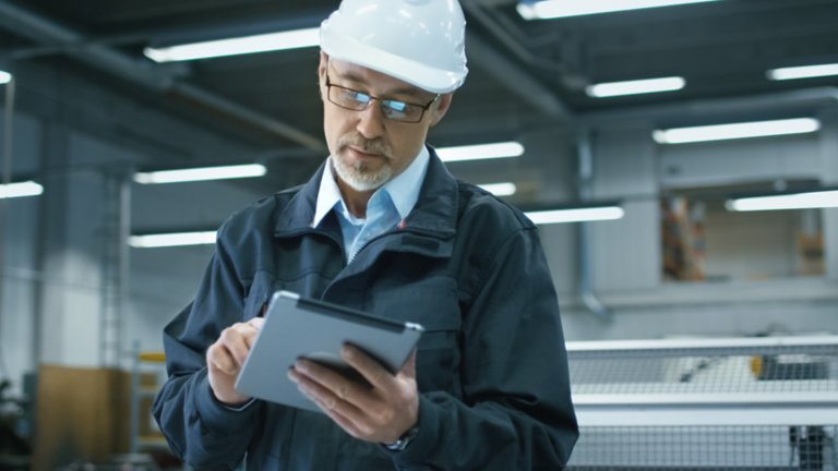 Engineer in a plant wearing glasses and a white hard hat viewing information on a tablet