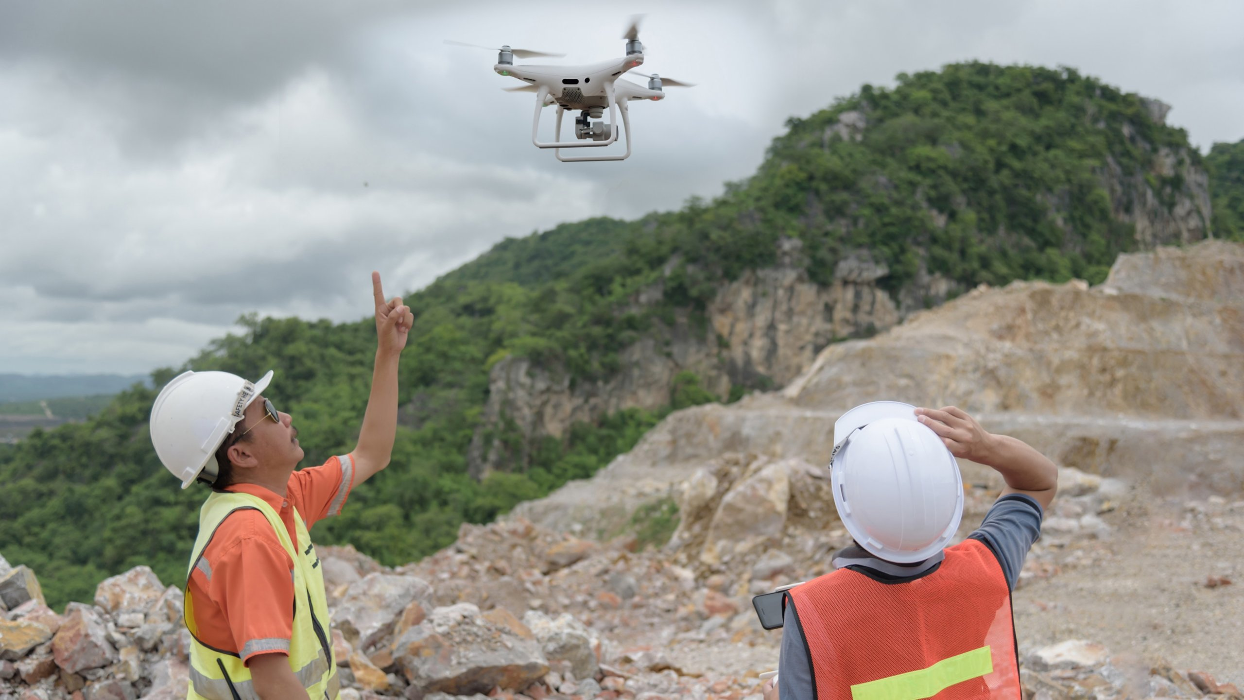 Man Operating Drone Flying by Remote Control to work at site rock mining.
