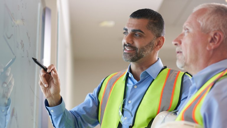 two men in yellow/orange safety vests discussing information whiteboard