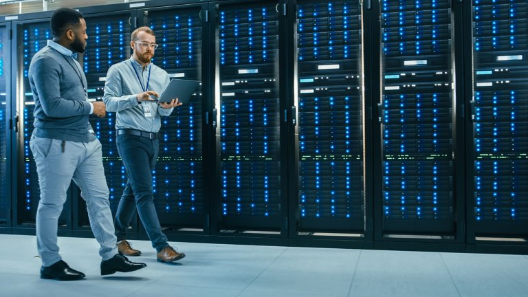 Two IT professionals walking through server room and consulting a laptop computer