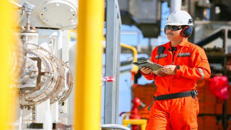 一名穿橙色防护服戴白色安全帽的男性员工正在查看石油钻塔零件并在平板电脑上做记录