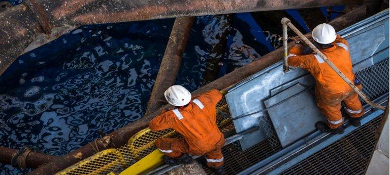 Deux employés portant des tenues de sécurité orange et des casques de chantier blancs regardant vers le bas du haut d'une plate-forme pétrolière