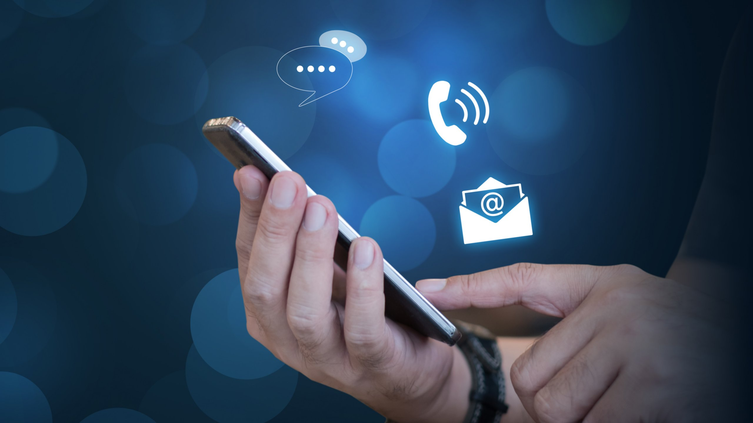 Businessman holding a mobile device with phone and email icons floating above the device to indicate contact options