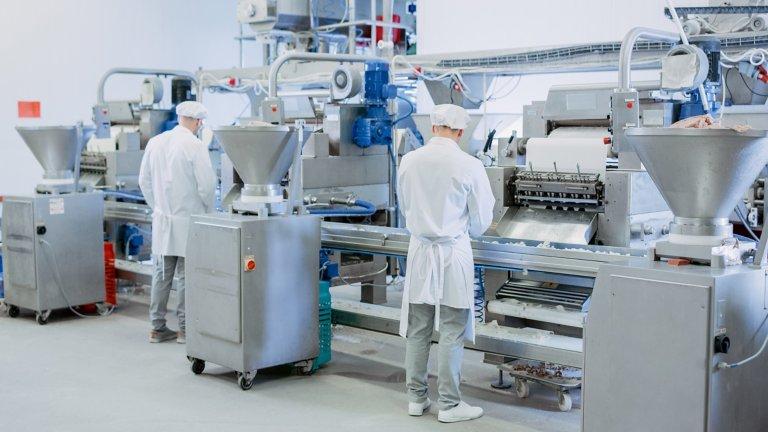 Lebensmittelverarbeitung mit Arbeitern, die Maschinenarbeiter beurteilen