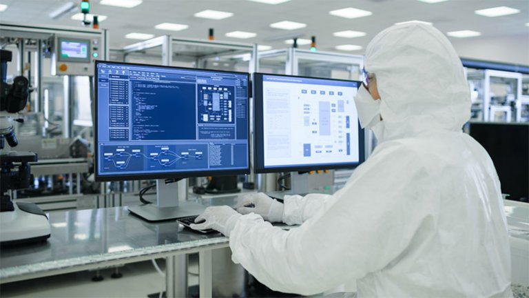 Gowned pharma worker at dashboard monitor