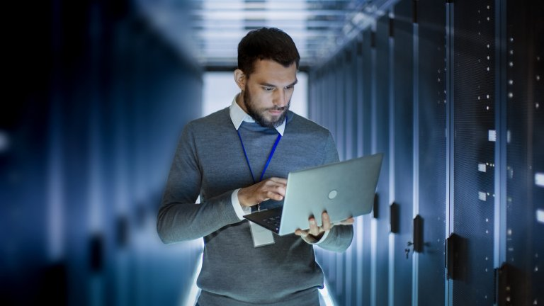 A Life Sciences professional reviews data on his laptop while standing near a row of servers.