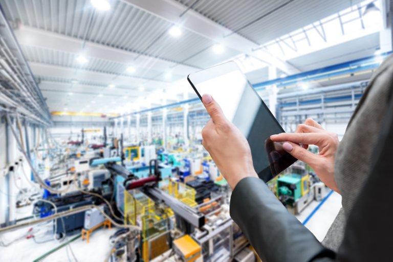 Eine Mitarbeiterin gibt Daten in ein Tablet ein, während sie einen Fertigungsbereich betrachtet