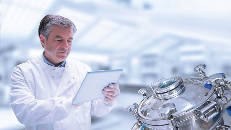 Pharmaceutical lab employee viewing data on a tablet