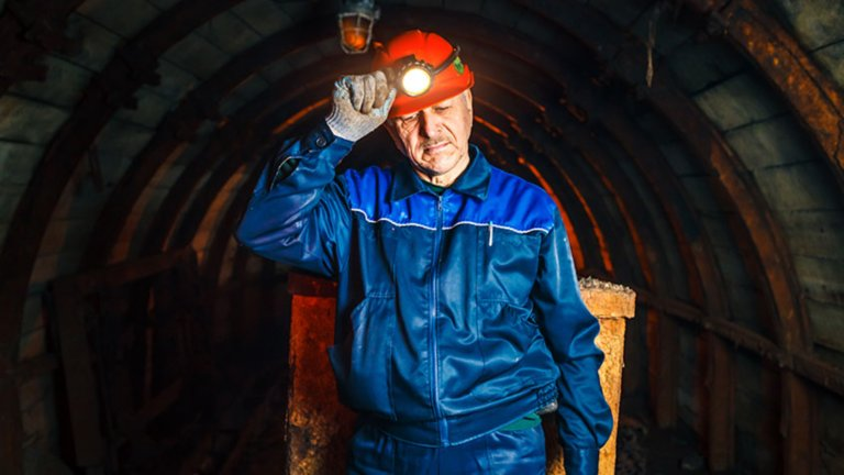 Male employee walking in mine wearing red hard hat with light