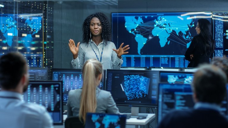 Woman speaking in control room to team by cybersecurity monitors