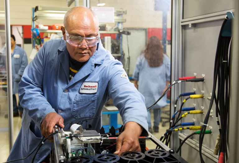 Male technician in blue coat performs automated testing on industrial drive during repair process