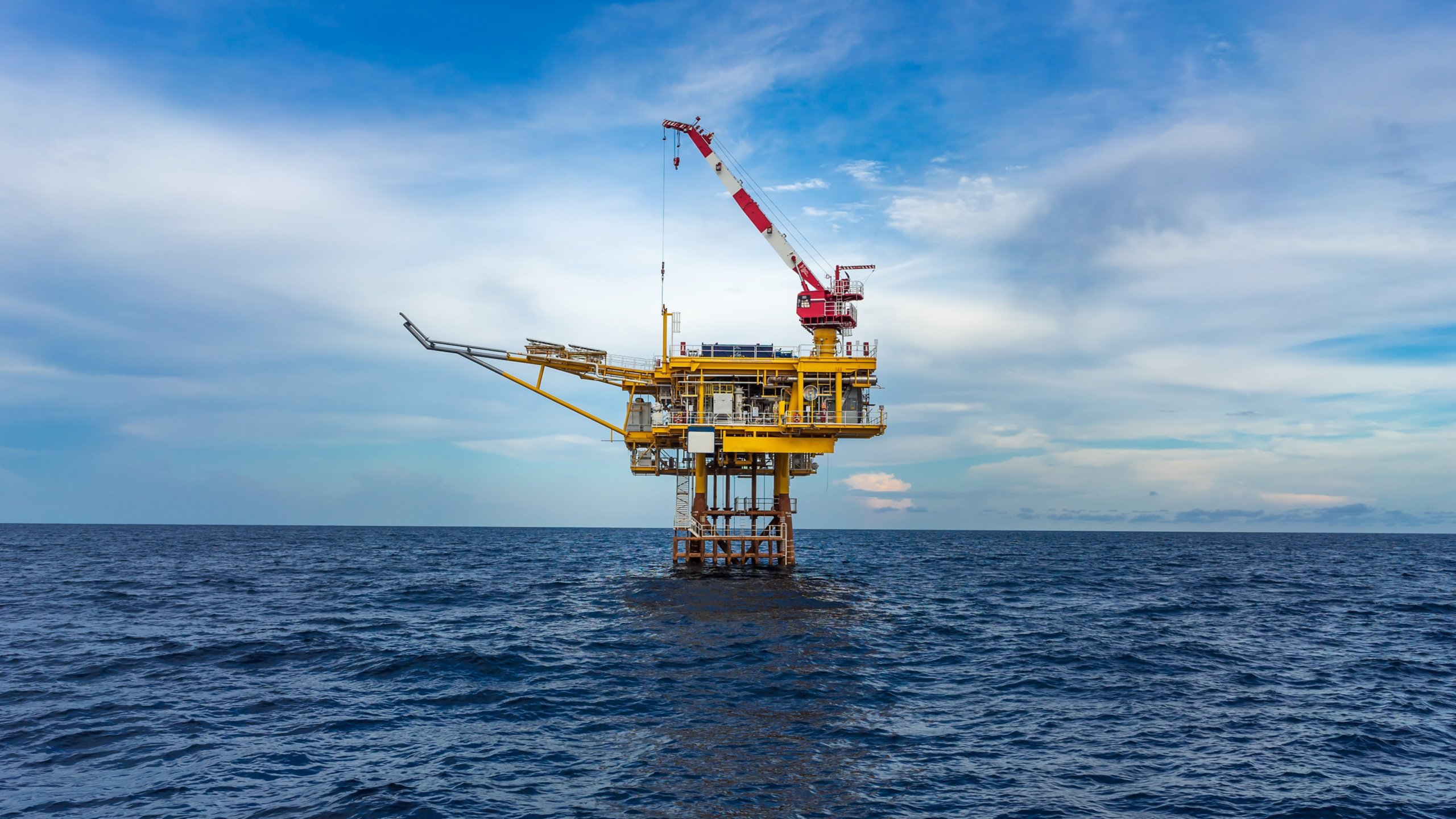 Offshore oil and gas wellhead remote platform with sea and blue sky background. Which produce raw gases and crude then sent to central processing facility far away. Oil and gas industry.