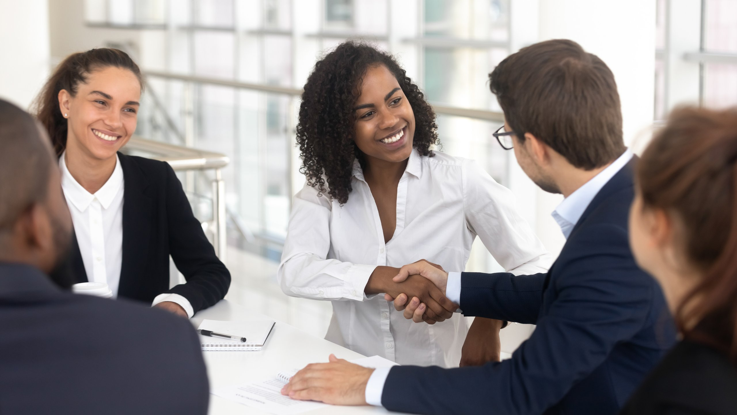 5 people in business casual clothing, man and woman shaking hands