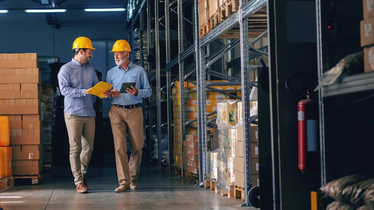 Two male employees wearing yellow hard hats conversing in a warehouse with packaged goods.