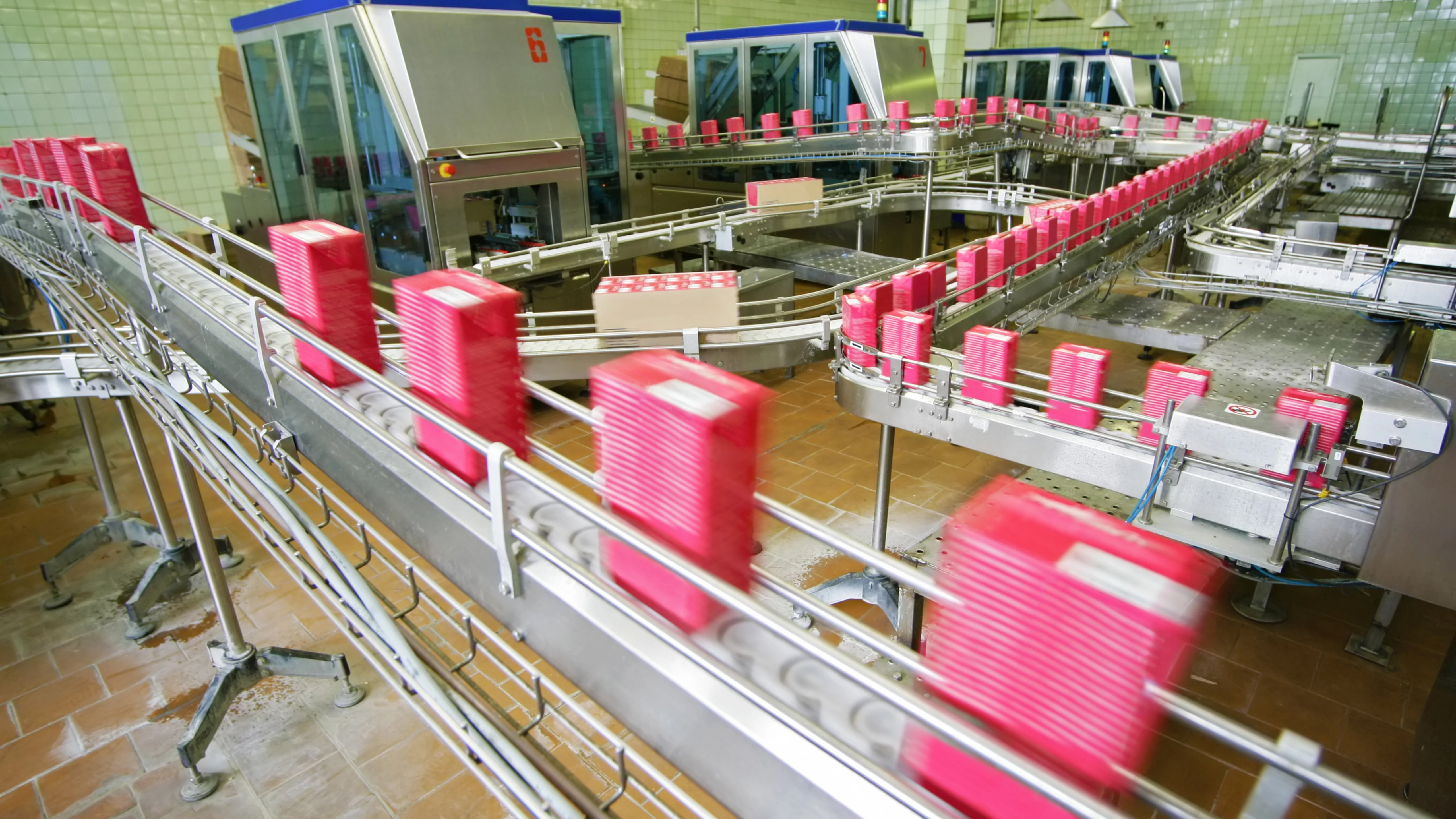 pink boxes moving on conveyor system in a factory