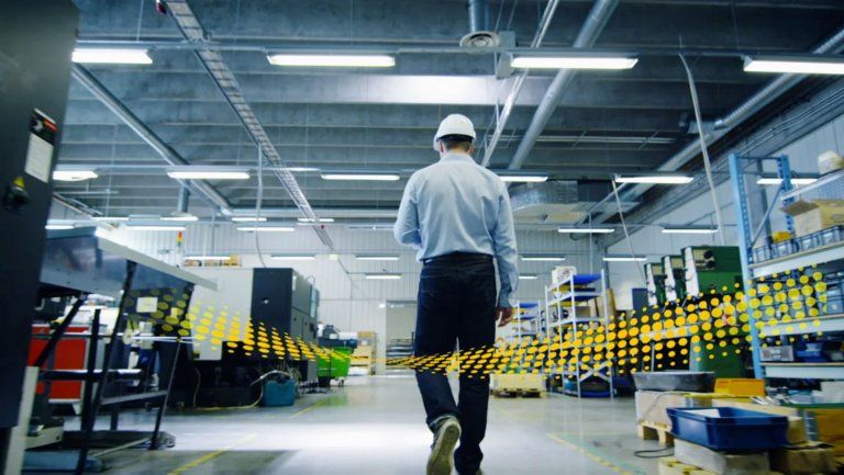 Male employee wearing a white hard hat walking through an aisle in a factory