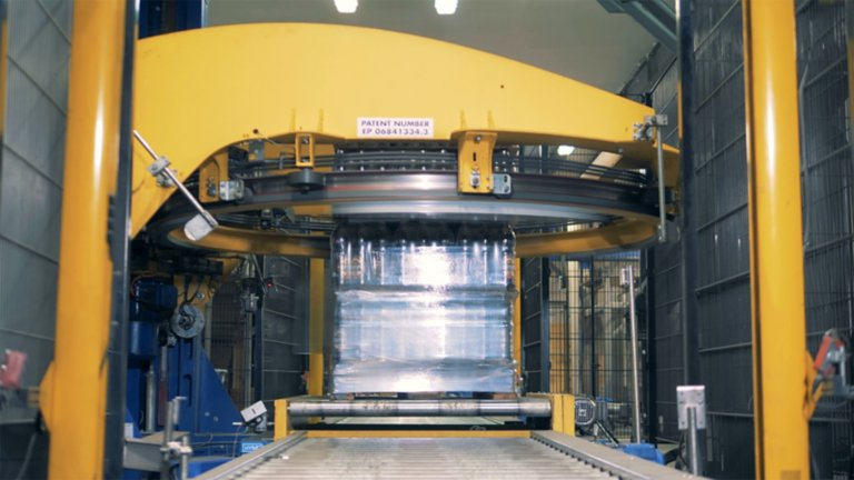 Zoomed in view of a yellow high-speed large pallet shrink wrapper machine with safety light curtain at the sides. The automated machine is wrapping a pallet of bottled drinks for delivery. This application example illustrates how you can leverage Rockwell Automation Micro Control solutions with Connected Components Workbench software to simplify standalone machine development and enhance operational productivity.