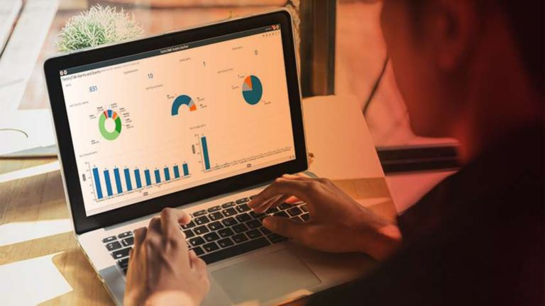 Employee working on his laptop and entering information into a program that has multiple graphs