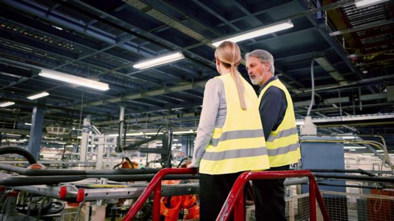 Automotive facility with two employees overseeing production