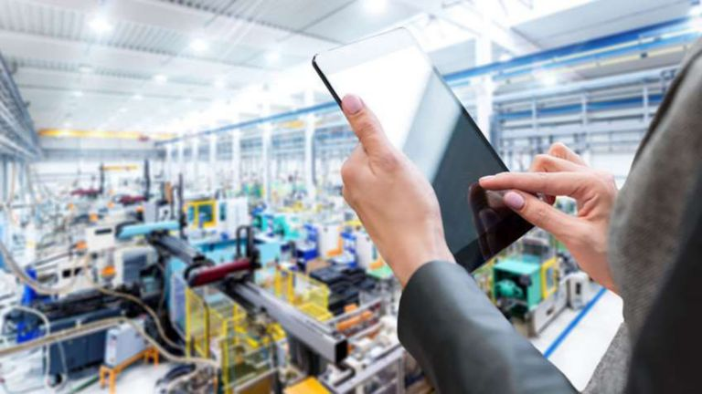 Employee using her tablet on factory floor